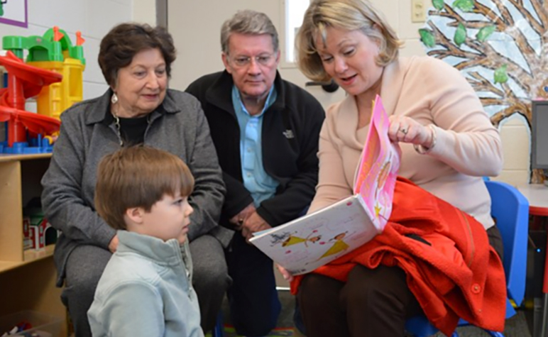 Cardinal Post January 2014: Grandparents reading book to SLS Student.