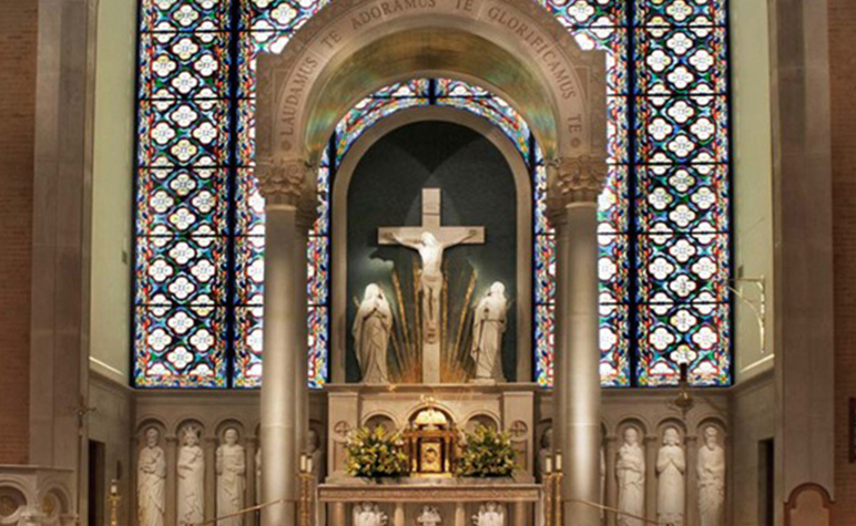 Catholic Church altar with stained glass and statues of Jesus on the cross along side the Virgin Mary